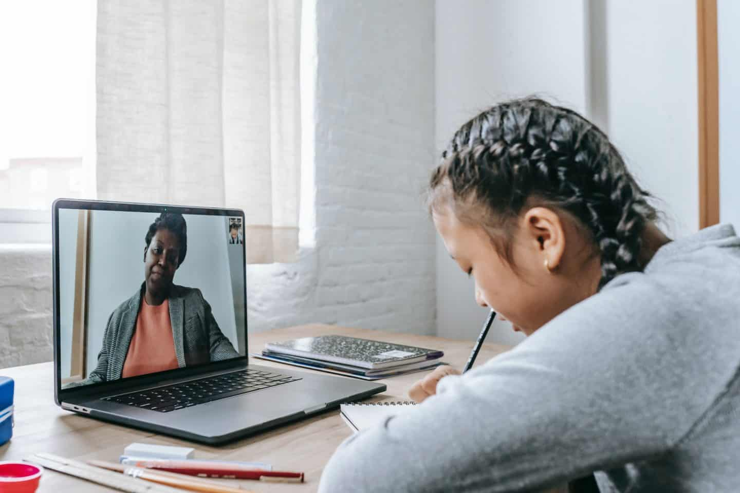 girl talking to tutor over facetime on a laptop