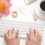 useful websites for students featured image of hands on a keyboard surrounded by a flower, coffee, lipstick, and desk accessories